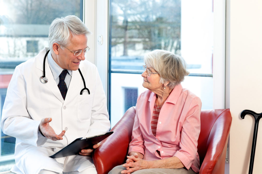 Male doctor in consultation with a senior female patient sitting having a discussion and offering a detailed explanation as they chat in front of a window in the hospital