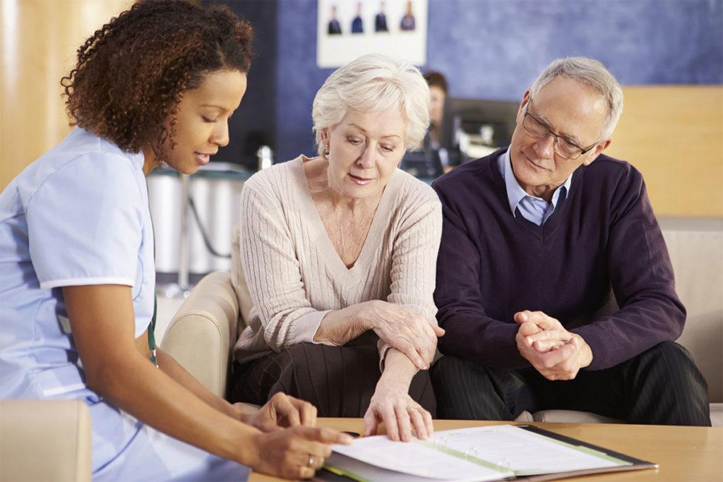Senior Couple Meeting With Nurse In Hospital