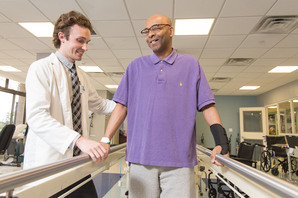 Therapist helps patient on parallel bars