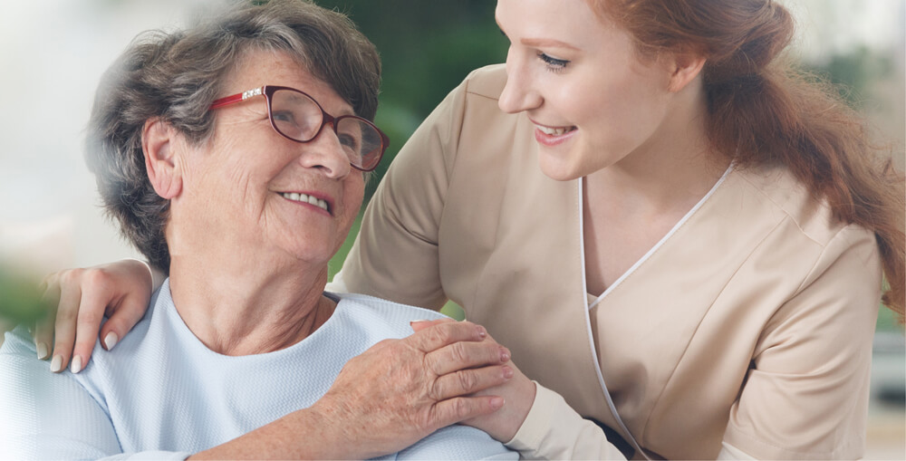 Photo of Professional helpful caregiver comforting smiling senior woman at nursing home